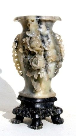 A Chinese figured grey soapstone vase carved with flowers on a pierced stand, 26cms (10ins) high.