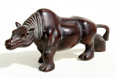 A Chinese hardwood carving in the form of a stylised rhinoceros, 28cms (11ins) long.