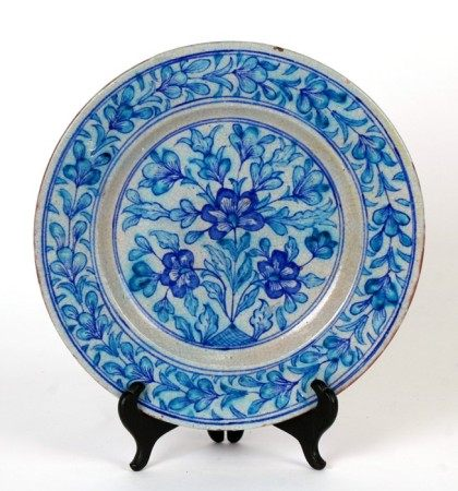 A Persian / Iznik plate decorated with flowers and foliage, 26cms (10ins) diameter.