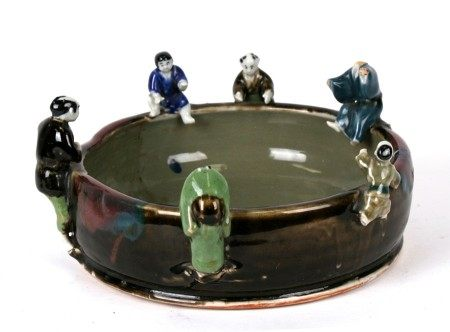 A Japanese bowl with applied figures to the rim, 27cms (10.5ins) diameter.