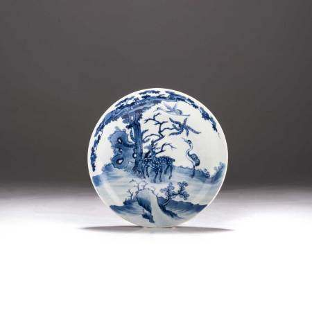 A CHINESE BLUE AND WHITE 'DEER AND CRANE' SAUCER DISH, QINQ DYNASTY, 18TH CENTURY Painted with two