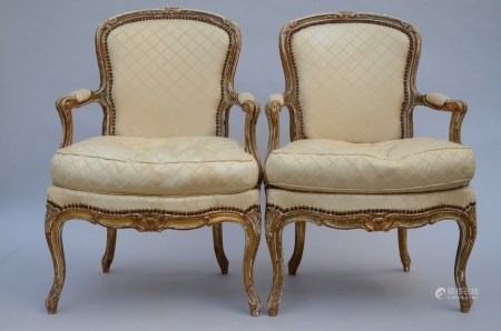 A pair of patinated Louis XV style armchairs