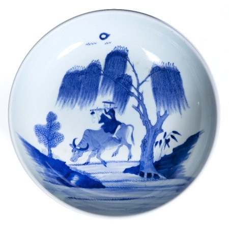 Blue and white dish Chinese, 19th Century depicting a musician sitting astride an oxen beneath a