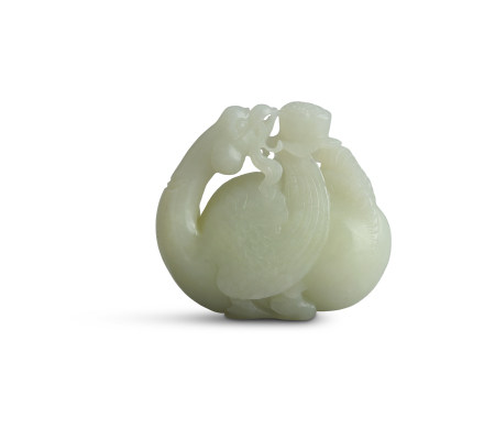 A CHINESE PALE JADE CARVING of mythical bird, modelled with returning glance and feeding on a flower