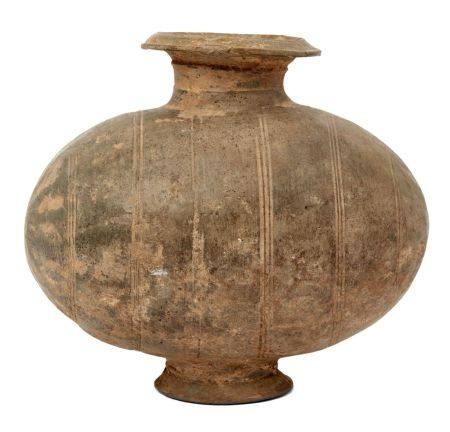 A Chinese grey pottery 'cocoon' jar, Han dynasty, decorated with linear bands raised on spreading