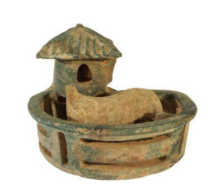A Chinese pottery model of a pig house, Han dynasty, modelled with a single pig standing in a pen,