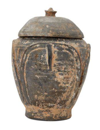 A Chinese grey pottery 'lotus leaf' jar and cover, Five Dynasties, the sides moulded with four