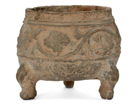 A Chinese grey pottery tripod vessel, Han dynasty, decorated in relief to the body with a band of
