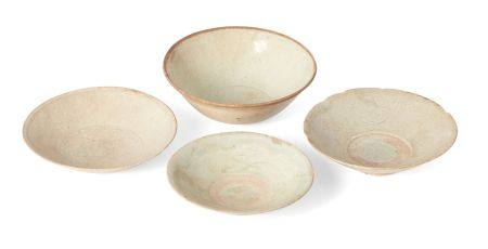 Four Chinese porcelain bowls, Yuan dynasty, each with pale blue translucent glaze, three with carved