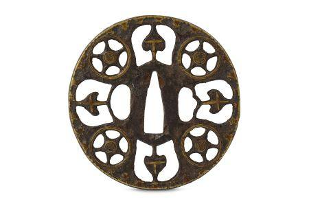 AN IRON MONSUKASHI NAMBAN TSUBA. Edo period. The round tsuba pierced and inlaid with brass in