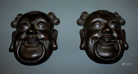 CHINE. Paire de HEURTOIRS en bronze à patine brune figurant deux visages. Epoque XVIIIe siècle.