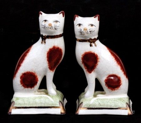 A pair of Staffordshire ware pottery figures in the form of seated cats, 11cms (4.25ins) high.