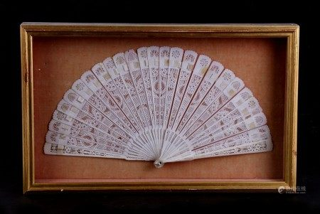 A Chinese Canton Export pierced bone brise fan, 30cms (12ins) wide, mounted in a glazed display case