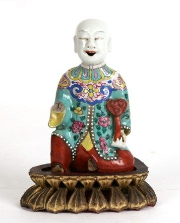 A 19th century Chinese famille rose incense holder in the form of a kneeling robed figure holding