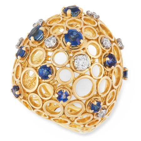A SAPPHIRE AND DIAMOND RING, ANDREW GRIMA 1968 of bombe design with circular openwork motifs, set