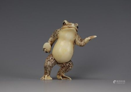 A Cattle Bone Carved Netsuke of A Frog Holding a Disc
