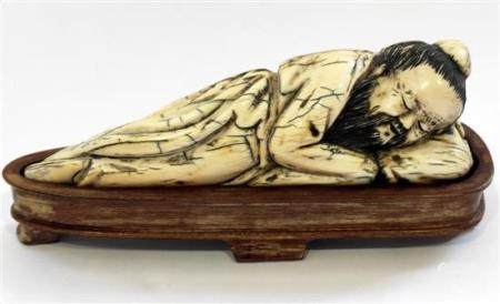 A Chinese Mammoth Ivory Carving of a Sleeping Sage, Lying on