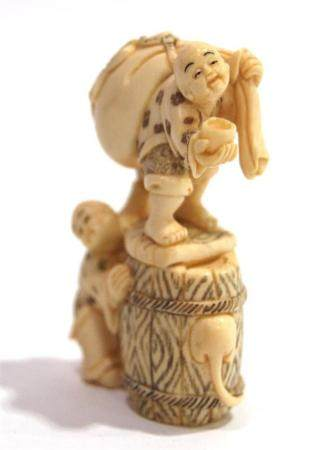 A Mammoth Ivory Ojime of Two Boys Climbing on a Barrel While