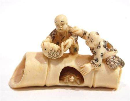 A Carved Mammoth Ivory Netsuke of Two Boys Balancing on a Ho