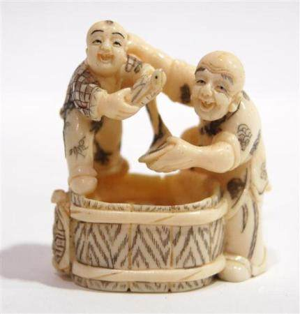A Carved Mammoth Ivory Netsuke of Father Trying to Dry Off a