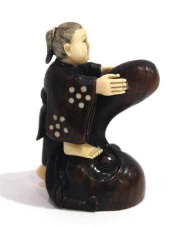 A Carved Wood & Mammoth Ivory Netsuke of a Figure Standing o
