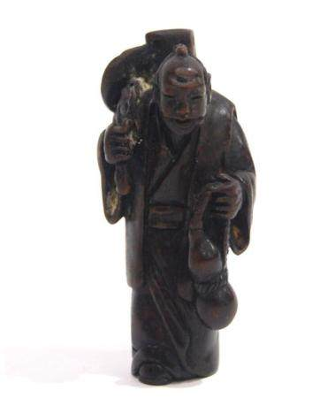 A Carved Wood Netsuke of a Figure Carrying a Gourd in One Ha