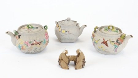 Three Japanese bisque teapots, each with relief moulded decoration of flora and fauna with