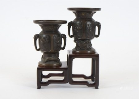 Two Meiji period bronze vases, of twin handled flaring shape, rising from the base above