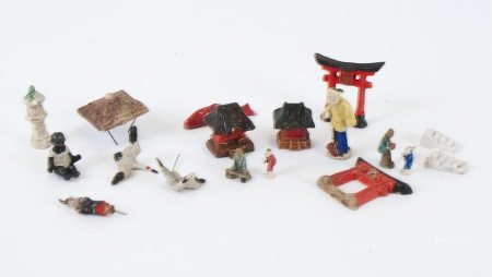 A collection of miniature Japanese porcelain figures, together with a small black baby, largest