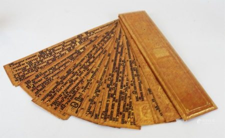 A South East Asian book, formed from crimson and gilt lacquer panels, profusely decorated with
