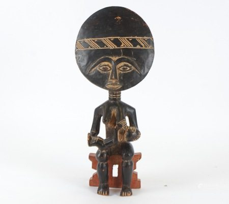 An Ashanti African tribal figure of mother with child sat upon a stool, height 51.5 cm