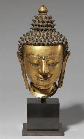 A precious Tibetan gilt bronze head of a Buddha. 14th/15th c