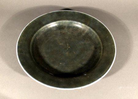 CHINE. ASSIETTE creuse en porcelaine à couverte vert épinard