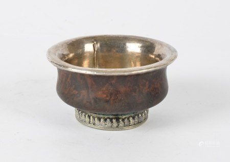 A Tibetan hardwood bowl, with white metal interior and footrim, height approximately 5cm, diameter