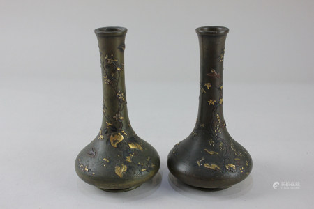 A pair of Japanese Meiji bronze vases depicting a naturalistic scene of a tree with birds and
