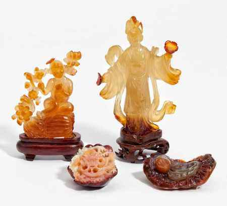 FOUR FIGURES CARVED FROM CARNELIAN.