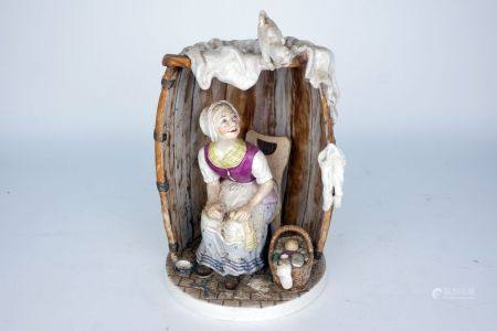 A Continental pottery figure of a woman seated in a barrel, 19th century, she modelled wearing a