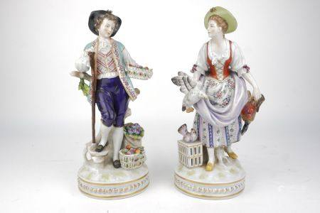 A pair of Continental porcelain figures of a boy and girl, 20th century, he wearing purple
