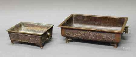 2 Ikebana-Schalen, Japan, um 1900, Bronze, patiniert, rechteckige Formen auf Füßen, je zwei Handhaben, Reliefdekore, Bodenmarken, 9.5 x 26 x 16.5 cm bzw. 11.2 x 41 x 24 cm