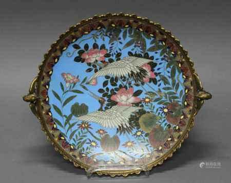 Platte, Japan, um 1870/1880, Cloisonné, dekoriert mit zwei Kranichen und Blumen auf blauem Grund, der Rand in vergoldete Bronze gefasst, zwei phönixförmige Henkel, ca. ø 31.5 cm