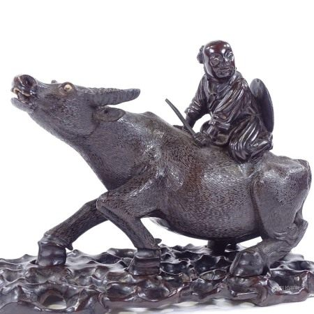 A finely carved Oriental hardwood figure of a boy riding a water buffalo, on original carved and