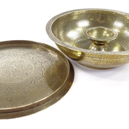 An unusual Islamic or Middle Eastern brass bowl, covered with engraved text inscriptions and