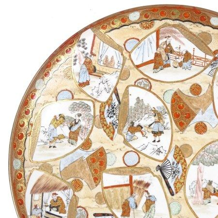 A Japanese porcelain charger, late 19th century, with hand painted panels in gilded surrounds, 3