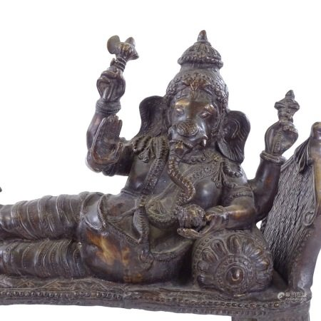 A large reproduction Indian heavy gauge patinated bronze figure of Ganesh reclining on a couch,