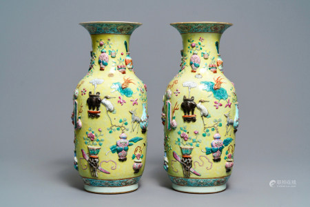 A pair of Chinese yellow-ground famille rose relief-decorated vases, 19th C.