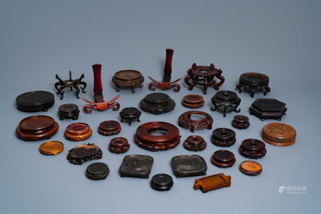 A collection of 33 Chinese carved wood stands, 19/20th C.