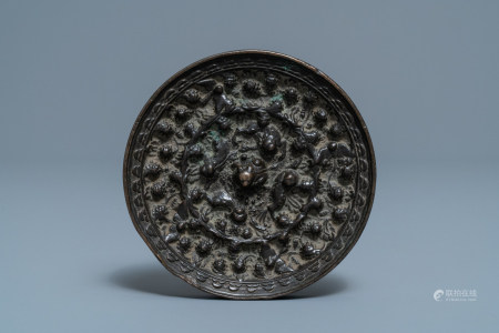 A Chinese bronze mirror with relief design, Tang