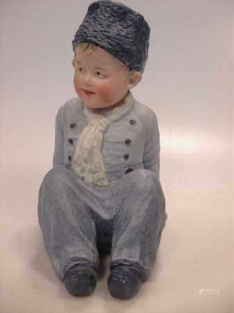 A Heubach piano doll of a young boy.