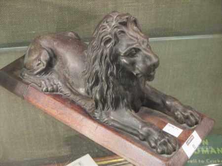 In the manner of Landseer, a bronze lion on wooden plinth