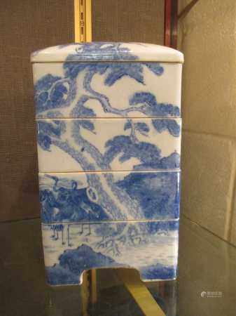 A 20th century Japanese porcelain four tier storage jar with lid, each side painted with
